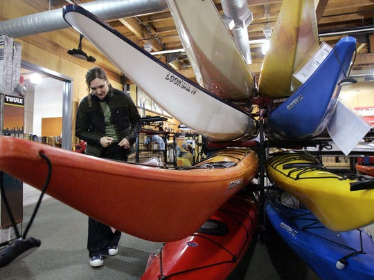 In this March 13, 2006, file photo, a woman looks over sea kayaks as she shops for a birthday present for herself at an REI store in Seattle. Outdoor retailer REI said Thursday, March 1, 2018, that it's halting future orders of some popular brands - including CamelBak water carriers, Giro helmets and Camp Chef stoves - whose parent company also makes ammunition and assault-style rifles.