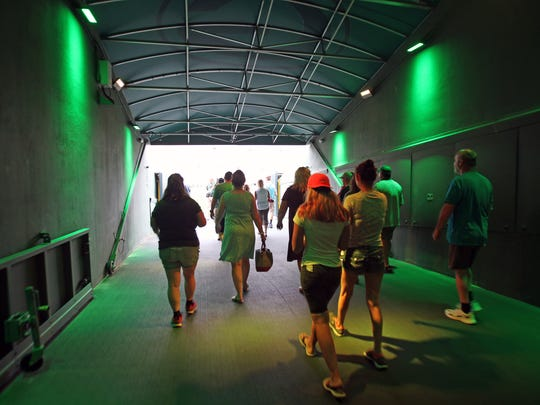 A group walks through the players tunnel onto Lambeau