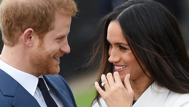 Britain's Prince Harry (L) poses with his fiancee, US actress Meghan Markle during a photocall after announcing their engagement in the Sunken Garden at Kensington Palace in London, Britain, Nov. 27, 2017. Clarence House said in a statement that the couple's wedding ceremony will take place in spring 2018. (Getty Images)