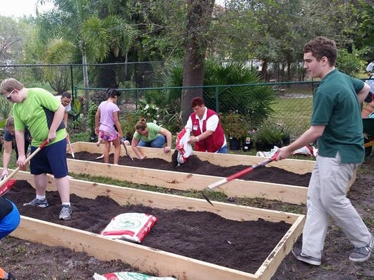Volunteers from Lowe's and students and staff of De