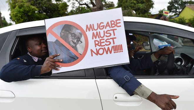 A man carries a placard as a demonstration calling for Robert Mugabe to step down marches toward the Zimbabwean State House.