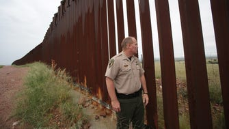 Cochise County Sheriff Mark J. Dannels checks out the border fence between Arizona and Mexico near the Huachuca Mountains.