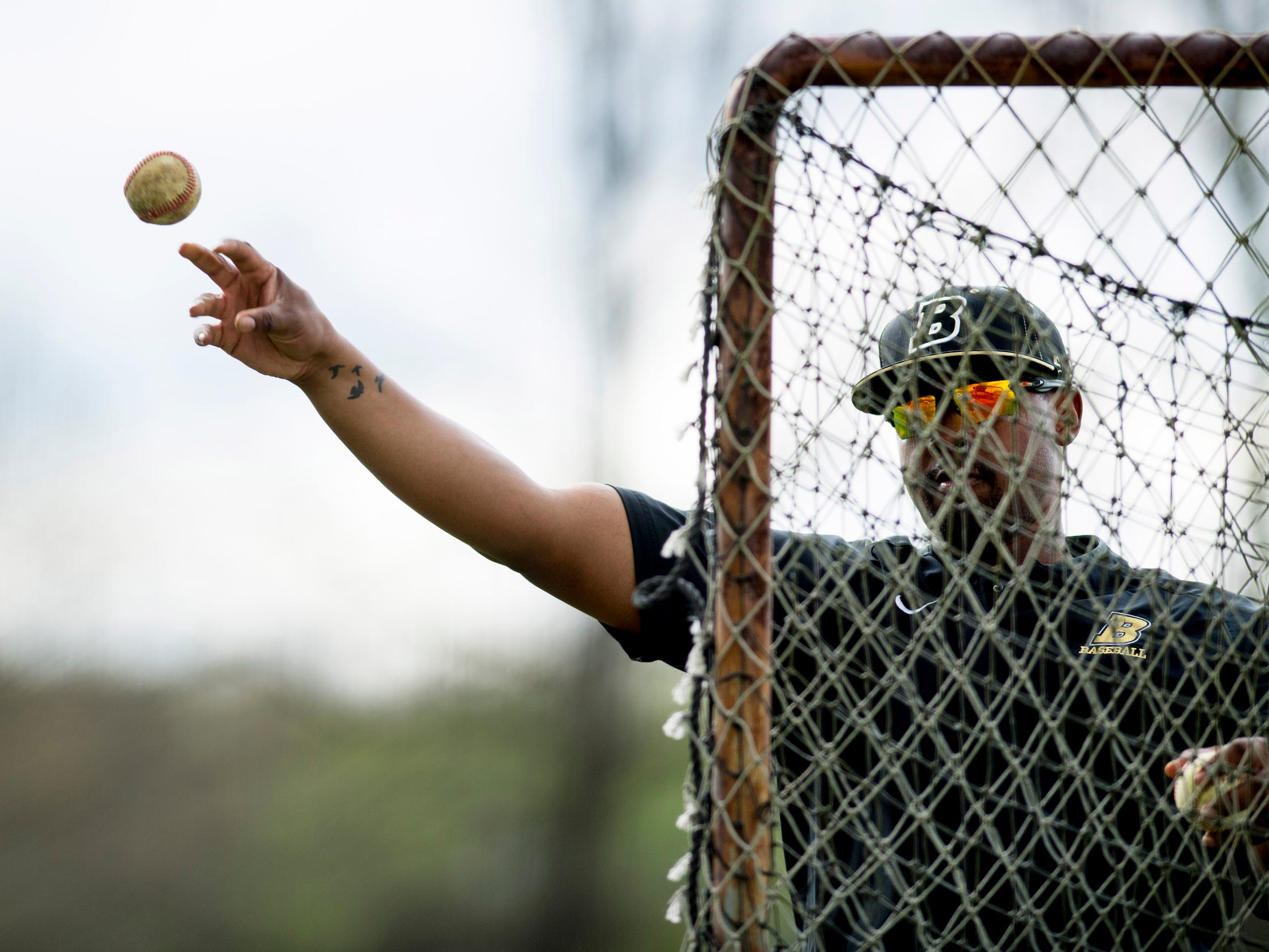 Boonville baseball coach Eric Barnes throws batting practice for his team Monday afternoon.