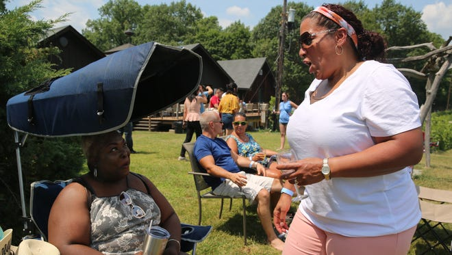 Thananyi Carr (left) and Pauline Boyin Bradley (right) catch up on Saturday at the 12th annual Hudson Valley July Sangria Festival at Benmarl Winery in Marlboro. Their group of friends gets together at the festival every year.