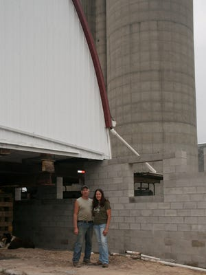 Dan and Marcy Wentworth, in front of their new barn and new concrete block wall, are hoping to bring their dairy cows back to the farm in a few weeks.