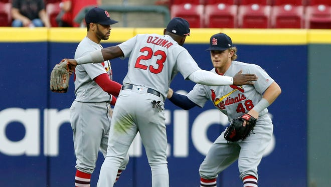 Cardinals center fielder Tommy Pham (left) and left fielder Marcell Ozuna (23) and right fielder Harrison Bader (48) react after the defeating the Reds at Great American Ball Park.