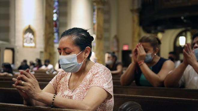 "Claudia Balderas, 51, prays for her brother, who died from COVID-19 in May, July 7 while attending the first in-person Mass in almost four months at Saint Bartholomew Roman Catholic Church in the Queens borough of New York. A Pew Research Center poll shows that while 2% of those surveyed say the coronavirus has weakened their faith, 25% declare the virus has deepened it. According to Gallup, 3% say their faith has ""gotten worse""; 19% say it's ""gotten better."""