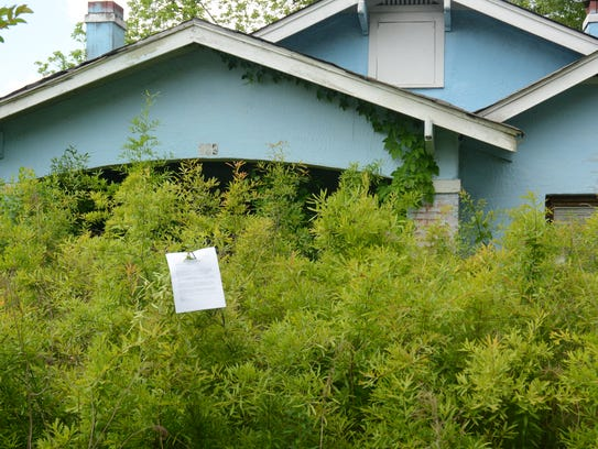 A notice from the city is attached to shrubbery outside an abandoned house about a block south of the Jackson Zoo's entrance on April 27, 2018. The notice says the city is authorized to demolish the property if the city doesn't hear from the property owner. There are several similarly blighted properties in the west Jackson neighborhood.