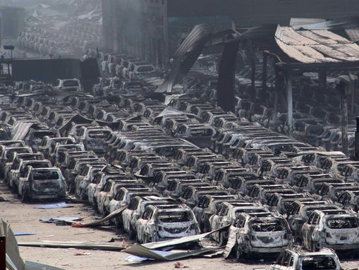 Damaged cars are seen at the site of a series of explosions