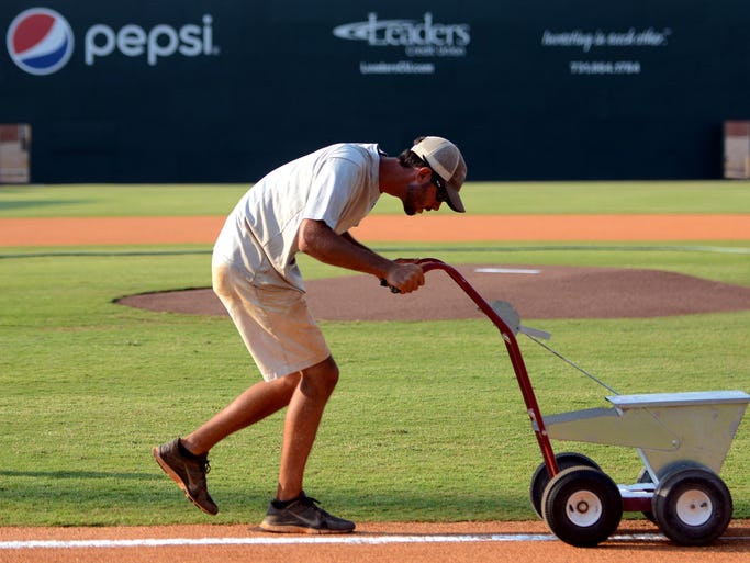 Jackson Generals' grounds crew member Shae Adams makes a chalk line between home plate and first base before the start of a Generals' game.