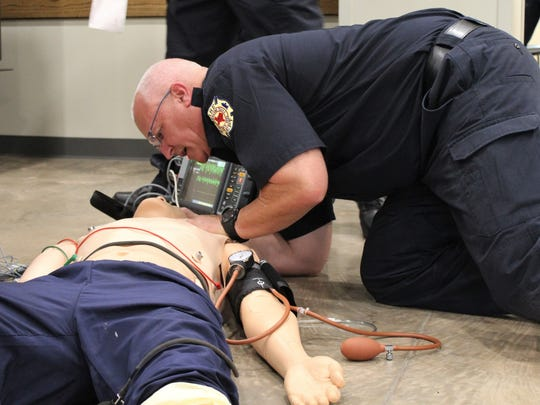 Kelly Davis, one of the crew on duty Monday at Station No. 3, demonstrates how emergency care would be given to a man (a mannequin, in this case) having a heart attack. Fire officials emphasized to Abilene Academy participants that timely care was essential in a positive outcome for the victim.