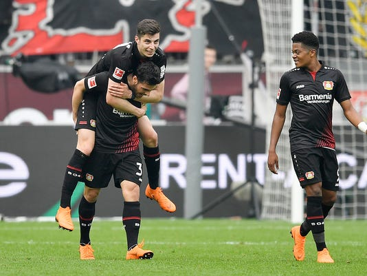 Leverkusen's Kevin Volland, left, carries his teammate Kai Havertz after scoring his side's second goal during the German Bundesliga soccer match between Bayer Leverkusen and Eintracht Frankfurt in Leverkusen, Germany, Saturday, April 14, 2018. (AP Photo/Martin Meissner)