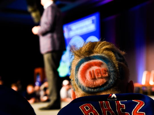 A fan looks on as Chicago Cubs' Chairman Tom Ricketts speaks to the crowd during the team's annual convention Friday, Jan. 18, 2019, in Chicago. (AP Photo/Matt Marton)