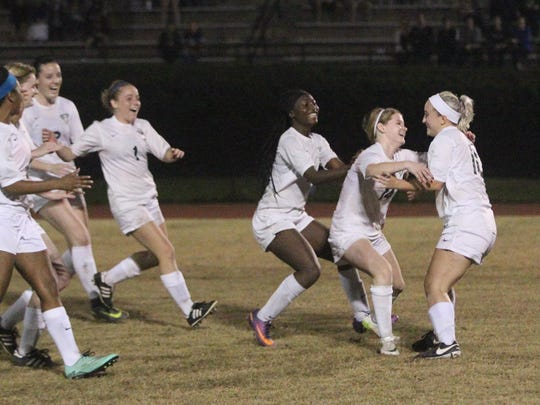 Lincoln's Erica Driver is mobbed by her team after scoring the winning goal during a penalty-kick shootout against Chiles on Wednesday in a District 2-4A semifinal.