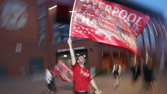 A Liverpool fan celebrates outside Anfield Stadium in Liverpool, England, Thursday night, after hearing Chelsea topped Manchester City to give Liverpool the Premier League title.