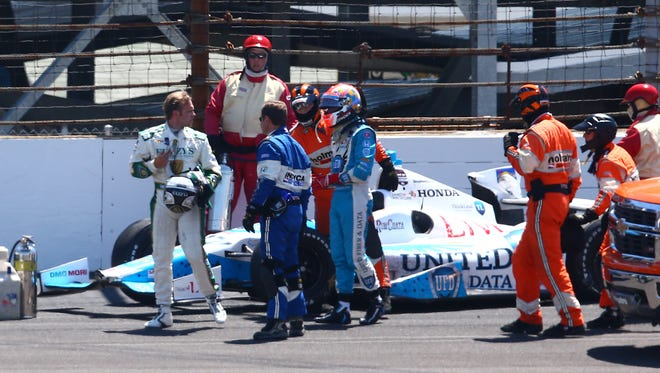 IndyCar safety crew members surround Ed Carpenter, left, and James Hinchcliffe, right, after they crashed during the 2014 Indianapolis 500.