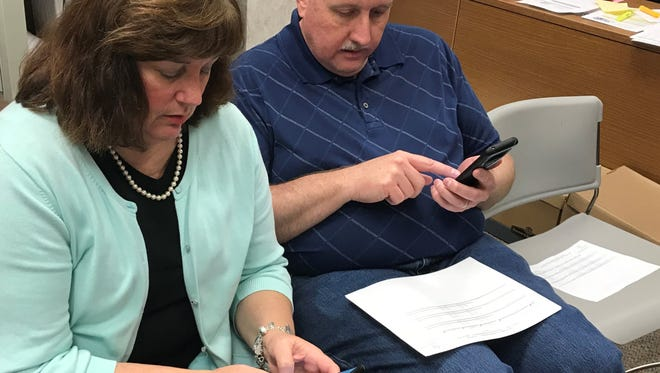 Shane Price and his wife, Carmen, text messages after election results were posted Saturday at the Taylor County Plaza. They were joined by son Allen at the election office. The Prices texted good news, as the three-term Abilene City Council member won a fourth term, unofficially with 83 percent of the vote against challenger Clinton Embry.