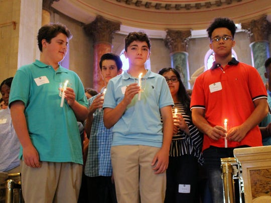 Standing with the 94 St. Elizabeth's freshmen at a candlelight prayer service are, from left, Joshua Christof, Joseph Castelli and Anthony D'Arcangelo.