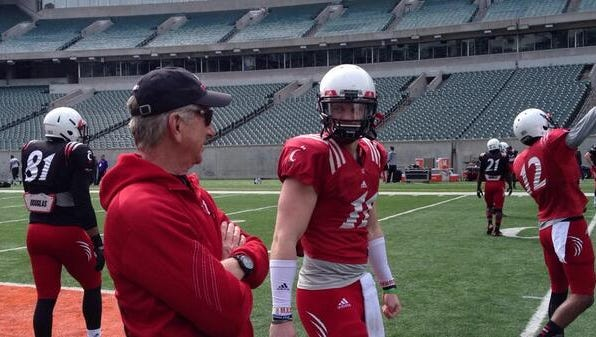 UC football coach Tommy Tuberville and quarterback Gunner Kiel talk before a spring scrimmage.