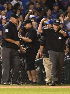 Umpires overturn a call that put Cincinnati Reds first baseman Joey Votto (19) out at first base to end the top of the ninth inning at Wrigley Field on Wednesday.