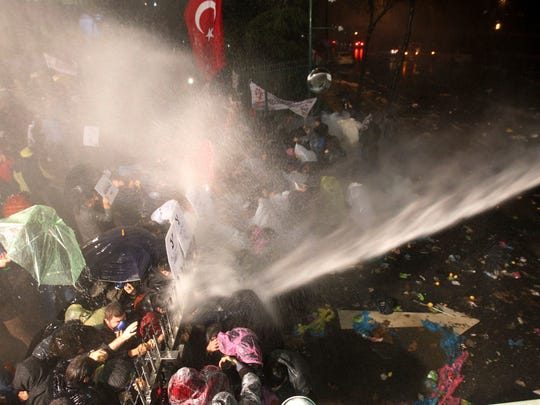 Riot police use tear gas and water cannon against people