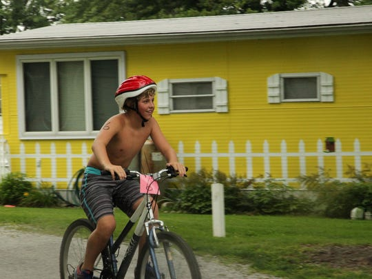 A triathlon participant brings it in after completing the five mile ride of the triathlon.