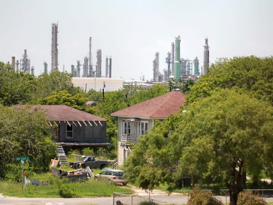These homes in the Hillcrest neighborhood are contrasted by stacks of refineries.