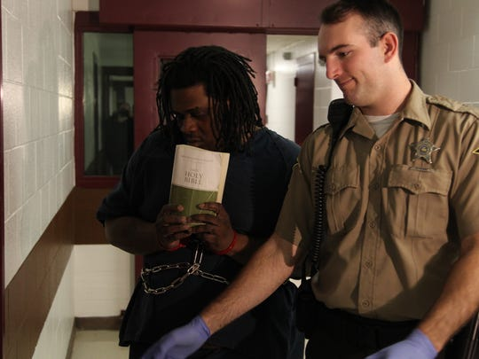 Aarron Christopher Vance, 35, clutches a copy of the Bible Wednesday, Jan. 25, 2017, before appearing in court on charges of murder, robbery and burglary, among many others.
