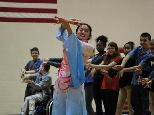 A performer demonstrates to Tecumseh students how to create a flower with their hands through traditional Chinese dance.
