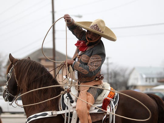 A cowboy performs lasso tricks during the 85th annual San Angelo Rodeo Parade that made its way through downtown San Angelo Friday, February 4, 2017.