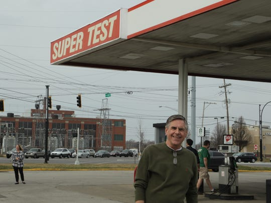 David Kenny stands beneath the Super-Test awning after the announcement of the winning Powerball ticket being sold at his store on Sagamore Pkwy on Thursday.