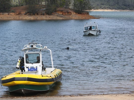 A Shasta County sheriff's diver, center, searches for