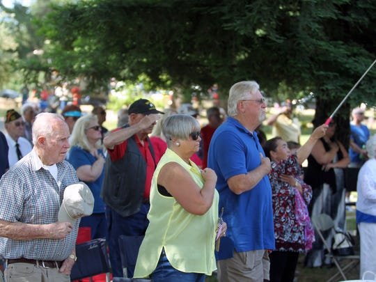 Attendees to Redding Memorial Park's Memorial Day observance on Monday salute as a Marine Corps Color Guard retires the American flag.