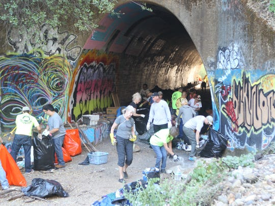 Volunteers gather Saturday morning to clear out a tunnel at Sulphur Creek.