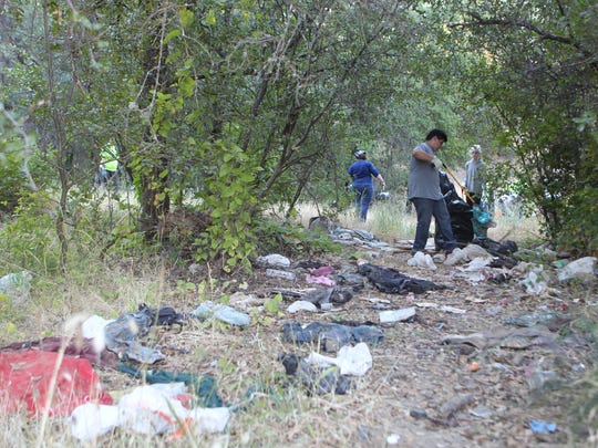 Volunteers pick up trash littered along the trail at