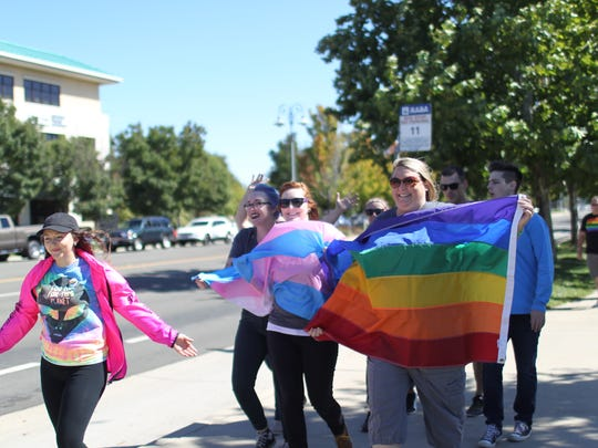 People wave flags as they return from a march on Cypress Avenue at Saturday's Redding Pride event.