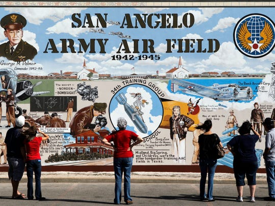 Passers-by stop to look at the military mural painted on the side of a building on the corner of Oakes Street and Concho Avenue in downtown San Angelo. The mural consists of three panels, each focusing on one of the three military installations in San Angelo: Fort Concho, the San Angelo Army Air Field and Goodfellow Air Force Base.