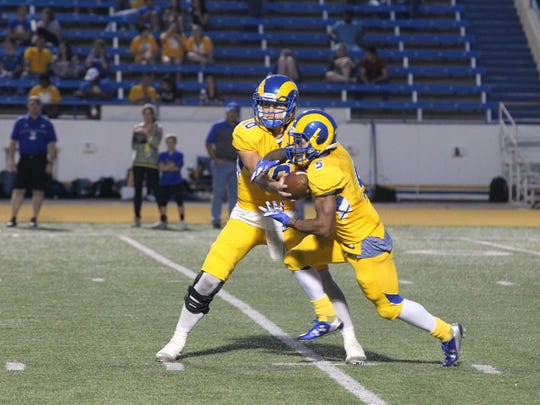 Angelo State University senior quarterback Jake Faber hands the ball off to fellow senior Josh Stevens during a 51-3 win against West Texas A&M on Senior Day at LeGrand Stadium at 1st Community Credit Union Field. Faber and Stevens were among 13 seniors who made their final home appearance on Saturday, Nov. 4, 2017.
