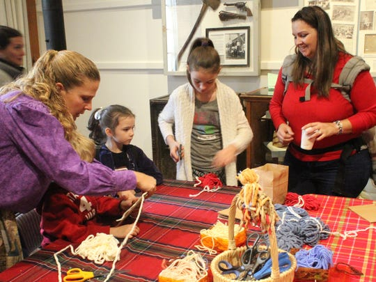 Children do yarn work at Shasta State Historic Park's Courthouse Museum on Saturday.