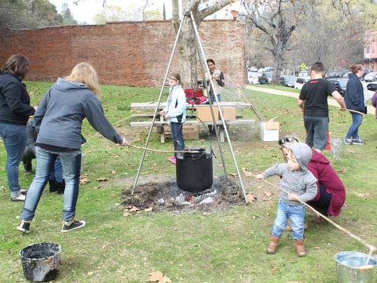 """Children try their hand at candle-making at Shasta State Historic Park during the annual """"Old Time Holiday"""" celebration."""
