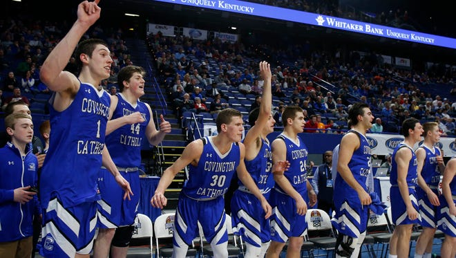 Covington Catholic players, including MVP C.J Fredrick, left, cheer in the final seconds of their win over Scott County in the championship game of the Whitaker Bank/KHSAA Boys' Sweet 16 basketball tournament played at Rupp Arena in Lexington, Ky. Sunday March 18, 2018.