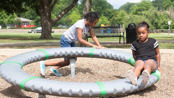 Kendal Aldrich (left) and Ava Grace Fraction play together Wednesday at Snow Hinton Park in Tuscaloosa.