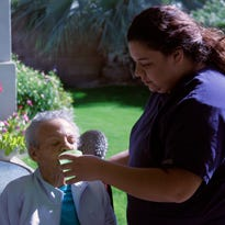 Bianca Colorado, a caregiver at Desert Cottages, gives water to a resident on Monday. Located in Indio, the facility focuses on providing care for individuals suffering from Alzheimer's disease and other types of dementia.