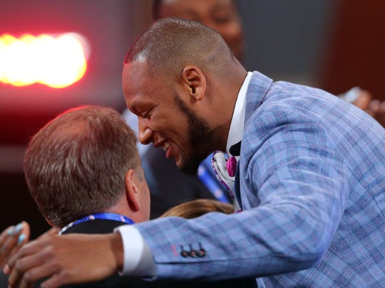 Adreian Payne gets a hug from Spartan coach Tom Izzo
