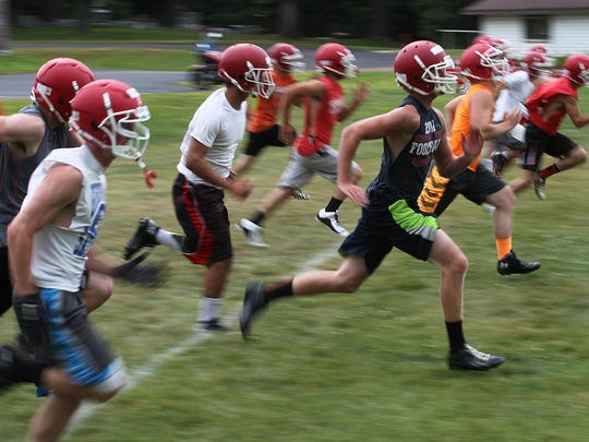Players sprint during a conditioning drill during the Greenwood Granton practice at Greenwood High School, Tuesday, August 4, 2015.