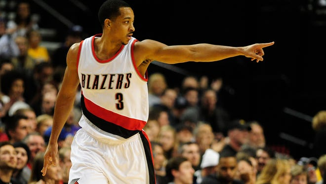 Portland Trail Blazers guard C.J. McCollum (3) points to the bench after hitting a three-point shot during the first half of an NBA basketball game against the Los Angeles Lakers on Saturday, Nov. 28, 2015, in Portland, Ore.