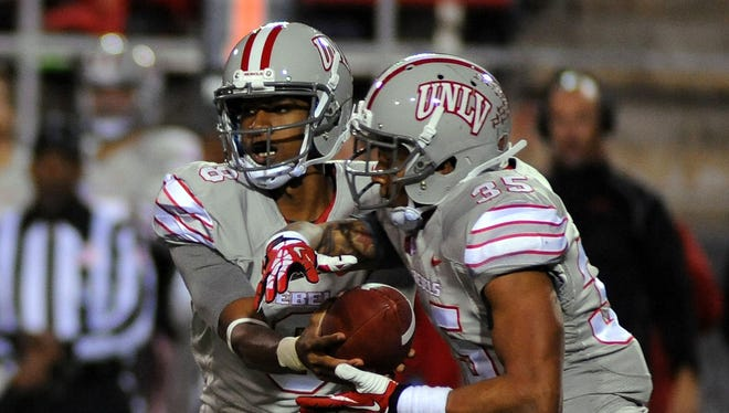 UNLV running back Tim Cornett (35) takes a handoff from quarterback Caleb Herring.