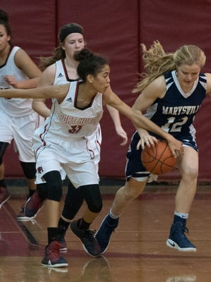 Port Huron's Kelsie Chapman reaches in on Marysville's Christy Melton to knock the ball loose Thursday, Dec. 22 during their basketball game at Port Huron High School.
