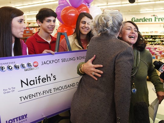 Tennessee Lottery CEO Rebecca Hargrove hugs Dana Naifeh, right, an owner of Naifeh's Food Market in Munford, Tenn. Hargrove presented Naifeh a $25,000 check for being the store that sold one of the three winning Powerball tickets.