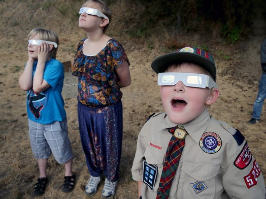 Sebastian Potter, 9, a Webelos Scout from  Pack 5239, watches the eclipse through slightly cloudy skies Monday at the Bremerton VFW hall.